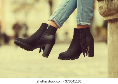 Elegant outfit. Closeup of stylish black suede ankle boots. Fashionable girl on the street. City lifestyle. Female fashion. Toned