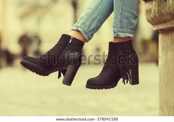 Elegante outfit. Closeup van stijlvolle zwarte suède enkellaarsjes. Modieus meisje op straat. Lifestyle in de stad. Vrouwelijke mode. Gestrakt
