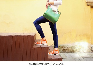 Elegant outfit, pretty slim woman in jeans and orange sandals with green leather handbag on the step platform on the street. Female fashion