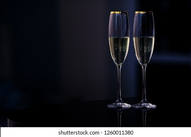 An elegant pair of glasses of champagne in the interior on the dark background. Holiday and night life concept.