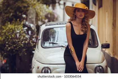 Elegant portrait of beautiful fashion woman wavy shine blonde long hair model in summer hat black dress and luxury accessories with bright makeup beside retro car in Trastevere Roma Italy. Soft light