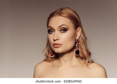 Elegant portrait of a middle-aged woman with big earrings with red stones. Gorgeous luxury statement accessory.