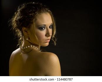 An elegant portrait of a woman on black.