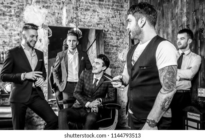 Elegant positive mens pose in barbershop. Black-white photo.