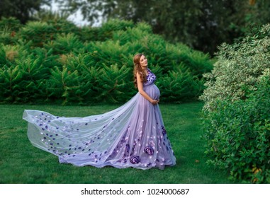 An elegant, pregnant woman walks in a beautiful garden in a luxurious, floral purple dress with a long train. Artistic Photography