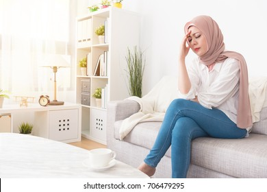 elegant pretty muslim woman feeling headache painful sitting on sofa couch relaxing.