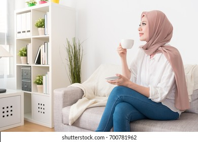 elegant pretty muslim woman sitting on sofa relaxing and holding coffee mug drinking hot espresso looking at window outside enjoying holiday time.