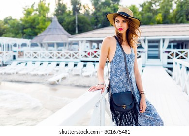 Elegant pretty slim woman with straw hat and long beach dress posing near luxury resort near the beach .  Wearing stylish  boho bag .