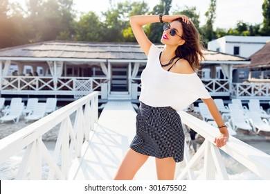 Elegant pretty slim woman in trendy summer outfit posing near luxury resort near the beach . Wearing stylish shirt high skirt and white t-shirt .