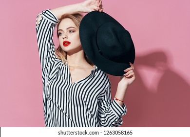 Elegant pretty woman holding a black hat on a pink background