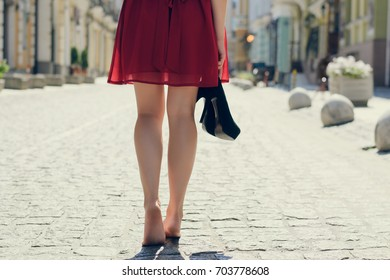 Elegant pretty woman with shoes in hands tired because of wearing high-heels walking along the street barefoot; close up photo of woman's long barefoot legs, view from back