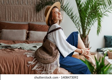 Elegant pretty woman in straw hat and white blouse posing at home, sitting on bed, morning mood. Home plants and palms. Macrame on wall. Boho style.