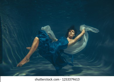 elegant pretty woman swims underwater like a free diver in a blue evening dress alone
