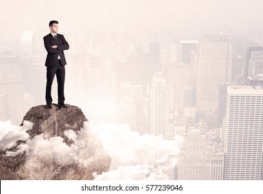 An elegant professional business male standing on top of a high cliff above the clouds looking at the city concept