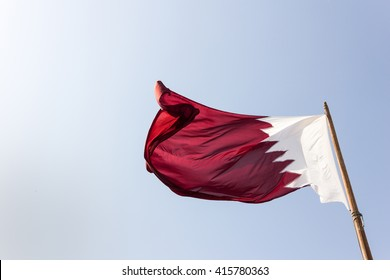 Elegant Qatar flag flying in the sky on a bright sunny day