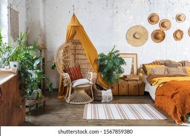 Elegantes und ruhiges böhmisches Zimmer mit gemütlichem Interieur, Korbsessel, Kissen, Kissen, Grünpflanzen in Blumenkästen, Bett und Teppich auf Holzfußboden