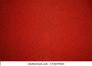 Elegant red canvas background with vignette and small dots. Scarlet backdrop for festive decoration and internet design. texture of sandpaper