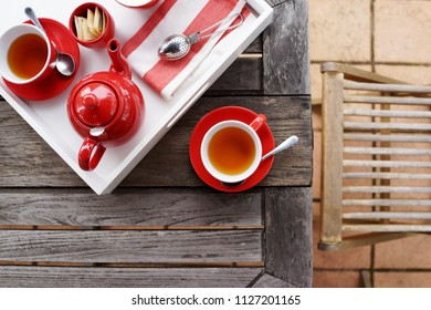Elegant red colour tea set with tea cup, saucer, tea pot, strainer, spoons, napkin and milk, arrange in white tray on wooden table, top view