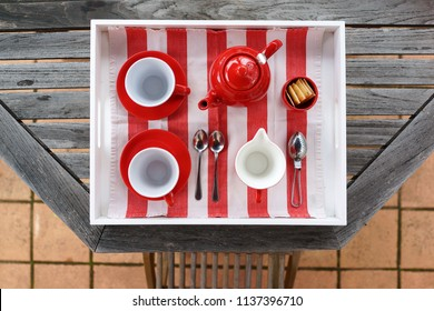 Elegant red colour tea set with tea cup, saucer, tea pot, strainer, spoons, napkin and milk, arrange on white tray, top view