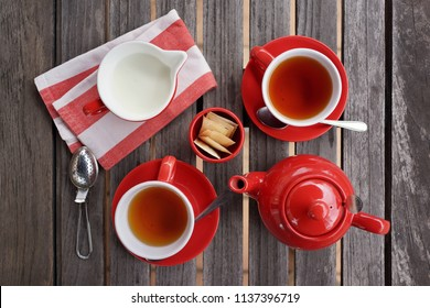 Elegant red colour tea set with tea cup, saucer, tea pot, strainer, spoons, napkin and milk, arrange on wooden table, top view