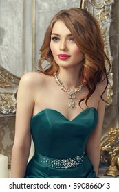 Elegant red hair girl with curls in green mermaid dress sitting on table in luxury interior and looking away. Fashion style portrait.