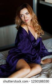 Elegant red haired woman with wavy hairs relaxing in her bedroom. Wearing elegant purple loungewear.