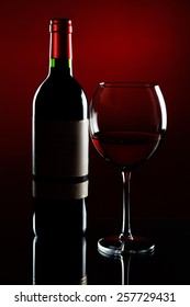 Elegant red wine glass with bottle on graduated red background