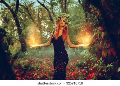 Elegant redhair girl witch conjures in the magic forest outdoors