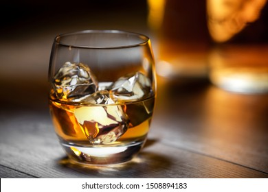 Elegant and refreshing glass of scotch bourbon whisky on ice with glowing illuminated golden bottles in background, copy space