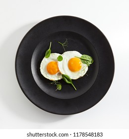 Elegant Restaurant Plate of Fried Eggs Decorated with Fresh Spinach Leaves and Young Pea Shoots on Flat Black Plate. Macro Photo of Healthy Nutritious Breakfast Isolated on White Background