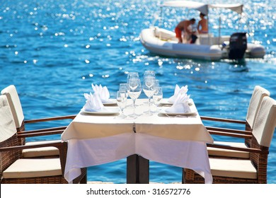 Elegant restaurant table waiting for customers by the sea; outdoor terrace in Perast, Montenegro