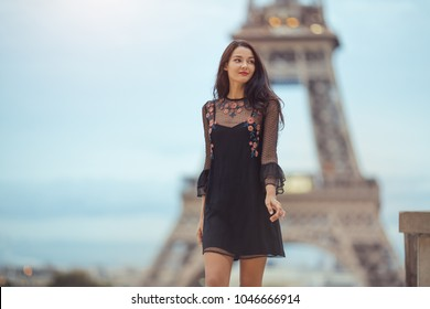 Elegant romantic Parisian woman in black sexy dress with flowers walking near the Eiffel tower at Trocadero view point in Paris, France on evening. Gorgeous mixed race Asian Caucasian girl enjoying