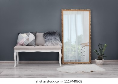 Elegant room interior with large mirror and bench