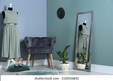 Elegant room interior with large mirror and comfortable armchair