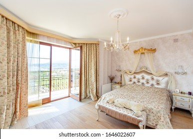 Elegant Royal white bedroom with a large double bed. White Carved back with a small canopy, white bedside tables with curved legs. Light striped Wallpaper. The lamps and chandelier