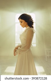 Elegant sad brunette woman with collected hair in retro hairstyle is standing in white castle room by window. Long vintage silk dress with sleeves. Fine art photography. Mysterious images princess