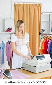 Elegant saleswoman standing at the cash register in a clothes store