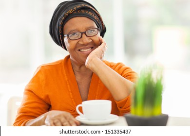 elegant senior african woman having tea at home