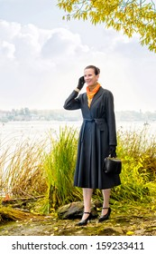 Elegant senior business woman with a mobile phone, a bag and an orange scarf, walking along the river, under the trees in autumn