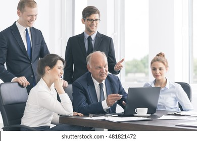 Elegant senior businessman showing something at a laptop to his young cooperatives