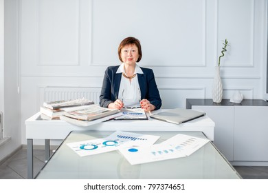 Elegant senior businesswoman dressed in the suit working with laptop and documents at the white office
