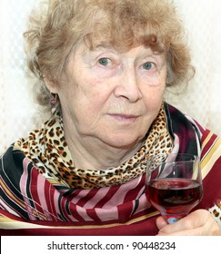 elegant senior lady holding a glass of red wine on a toast