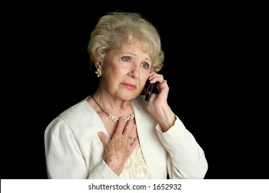An elegant senior woman hearing sad news over the phone.