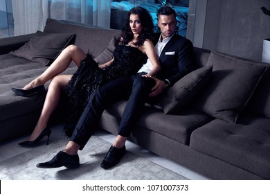 Elegant, sensual couple sitting on the couch