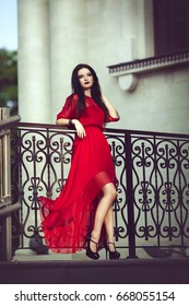 Elegant sensual sexy young woman in red dress posing near a handrail.