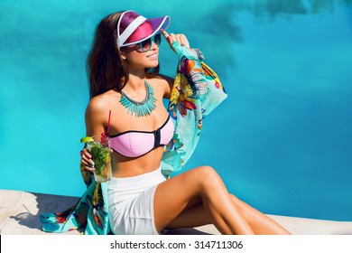 Elegant sensual tan  woman   in bright dammer vacation clothes sitting near big pool and drink exotic  cocktail . Bright summer colors. Stylish accessories and sunglasses. Beach party.