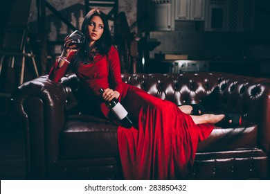 elegant sensual young brunette woman in red dress sitting on leather sofa, specially toned