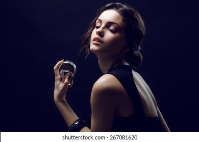 Elegant sensual young woman holding perfume. Fashion photo of young magnificent woman. Girl posing. Studio photo. Perfect Skin. Professional Make-up.Makeup. Fashion Art.Vogue Style.