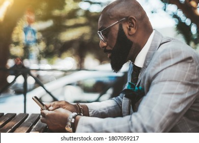 An elegant serious bald mature black guy with a well-groomed beard, in eyeglasses and a fashionable suit, is sitting outdoors at a wooden table of a street bar and using a smartphone to read a message