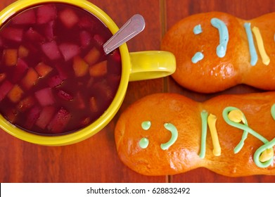 Elegant setup traditional tasty latin american guagua breads, colorful sugar decorations, bowl with colada morada berry juice next to it, day of the dead concept